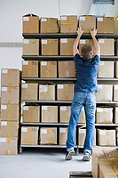 Man filing cardboard boxes in storage