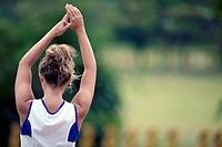 sports playing girl with arms raised, shot from behind
