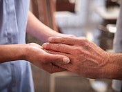Nurse examining older mans hands