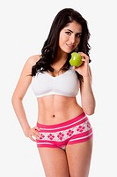Beautiful happy young woman fit slim in shape with apple for good health standing showing abs and body, weight conscious diet nutrition, isolated