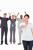 Businesswoman with cheering colleagues behind her giving approval against a white background