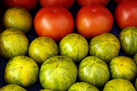 Green zebra tomatoes with red tomatoes in the back for sale at a farmer´s market