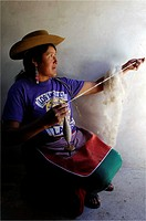 A woman spins wool for craft textiles