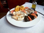 Mediterranean plate of food that includes babaganoush,dolmades,hummus,tomatoes and carrot salad