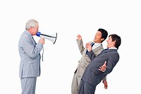 Senior businessman with megaphone yelling at his employees against a white background