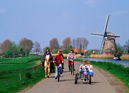 Kids riding bicycle on country road along canal with windmill in Schermerland, Holland                                                                ...
