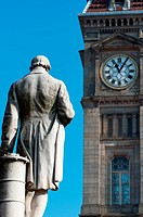 A statues of James Watt looks towards the 'Little Ben' Clock tower on Chamberlain Square, Birmingham, England