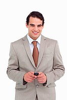 Smiling salesman holding his cellphone against a white background