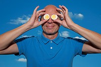 Balding Man Holding Slices of Eggs in Front of Eyes