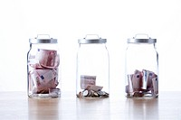 Three glass jars filled with European union currency against white background