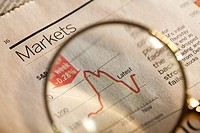 Magnifying glass enlarging stock market chart