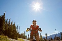 Adult female smiles and bikes around a mountain trail that is surrounded by evergreens, low angle