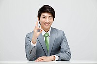 Portrait Of Smiling Asian Businessman Showing Ok Sign