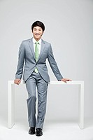 Portrait Of Smiling Asian Businessman Leaning On Desk