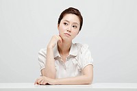 Asian Businesswoman Sitting In Front Of Desk With Head On Chin