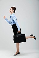 Asian Businesswoman In Hurry Holding Suitcase In Hand