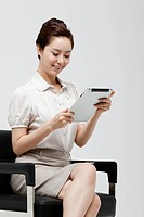 Asian Businesswoman Sitting In Chair And Looking At Digital Tablet