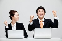 Asian Businesswoman Looking At Excited Businessman Sitting At Desk With Laptop