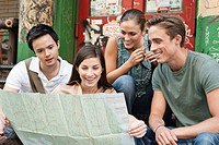 Friends looking at map in street