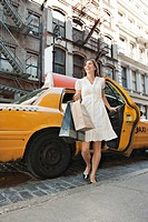 Woman with shopping bags getting out of cab (thumbnail)
