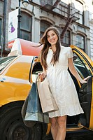 Portrait of woman with shopping bags getting out of cab (thumbnail)