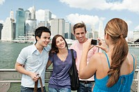 Friends taking pictures in front of Manhattan skyline, New York City, USA