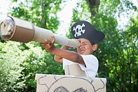 Boy 5_6 dressed up as pirate looking through spyglass