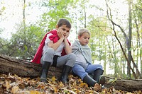 Two boys 5-6 in costumes sitting on log in forest (thumbnail)