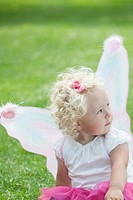 Portrait of cute girl 3_4 in butterfly costume sitting on grass