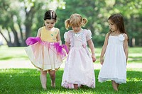 Three girls 3-4 in costumes walking on grass (thumbnail)