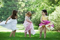 Three girls 3_4 in costumes dancing on grass
