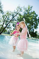 Two girls 3_4 in fairy costumes playing at pool