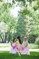 Three girls 3_4 in costumes dancing in park