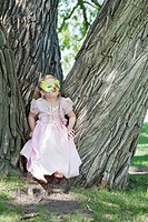 Girl 3-4 wearing costume and mask sitting among big trees (thumbnail)