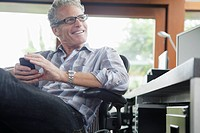 Middle-aged man with cell phone at desk (thumbnail)