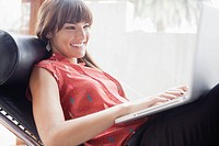Smiling woman sitting in armchair and using laptop