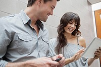Man and woman watching digital tablet and smiling