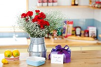 Wrapped Gift Box And Bunch Of Flower On The Kitchen Counter