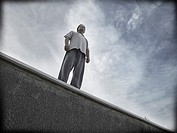 Challenging single man standing on a ledge
