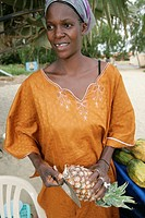 Woman fruit vendor in traditional dress peels pineapple The Cape beach Bakau The Gambia