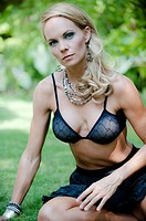 34 year old blond woman in sexy clothes sitting on the grass in a backyard looking at the camera