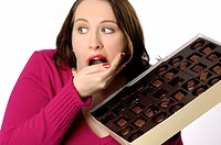 Humorous image of a woman who is glancing sideways to make sure no one is looking while she indulges in a large box of chocolate candy