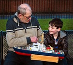 Young boy and old man discussing model boats in a park