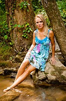 34 year old blond woman in a short flower print dress sitting on a rock by a small creek looking at the camera