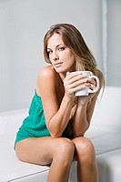 Portrait of a beautiful and sexy blonde women enjoying a coffee at home