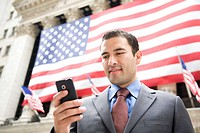 Businessman texting in front of American flag