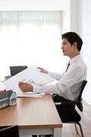 Businessman holding blueprint at desk