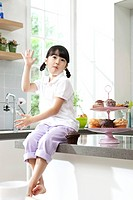 Little girl having muffin sitting on kitchen counter