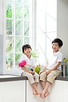 Little girl and boy sitting in kitchen counter