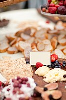 Wooden platter with figs, cheese spread, crackers and berries. Blank white card for sign.
